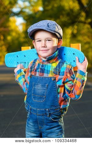 Smiling boy holding color plastic penny board skateboard outdoor