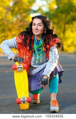 Smiling woman sitting near color plastic penny board or skateboard outdoor