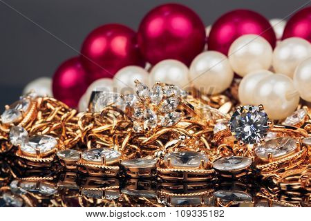 Various gold jewellery on black background