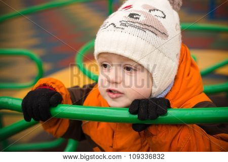 The Little Boy In A Warm Cap And A Jacket Holds An Iron Hand-rail At A Playground