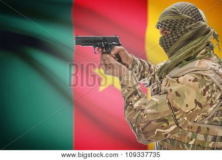 Male In Muslim Keffiyeh With Gun In Hand And National Flag On Background - Cameroon