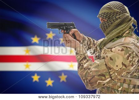 Male In Muslim Keffiyeh With Gun In Hand And National Flag On Background - Cape Verde
