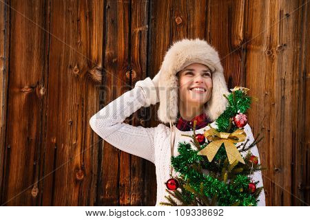 Woman With Christmas Tree Near Rustic Wall Looking On Copy Space