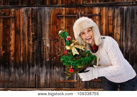 Smiling Woman With Christmas Tree In Front Of Rustic Wood Wall