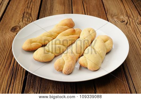 Twisted Cookies On White Plate On Old Wooden Table
