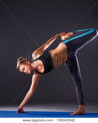 Young woman doing yoga exercise on mat