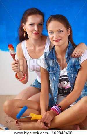 Two Happy beautiful young women doing wall painting,