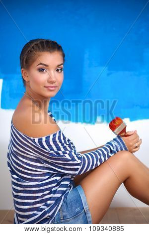 Portrait of female painter sitting on floor near wall after painting.