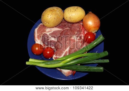 Fresh meat and vegetables on blue plate on black background