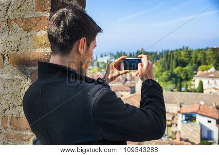 Young man taking photo with cell phone of the landscape