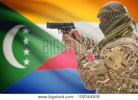 Male In Muslim Keffiyeh With Gun In Hand And National Flag On Background - Comoros