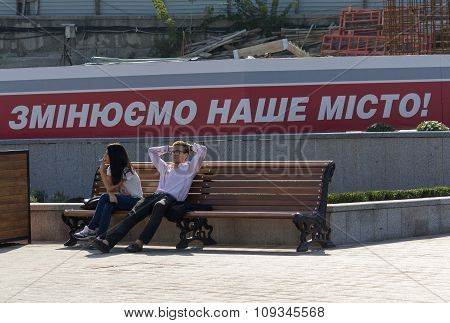 Kiev, Ukraine - September 18, 2015: Man And Woman Resting On The Bench On The Background Of The Slog