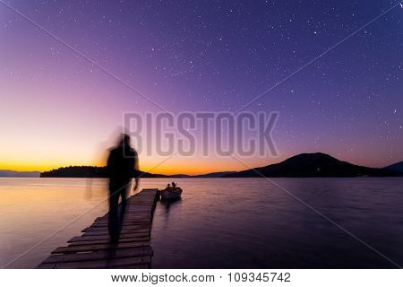 Man ghosty silhouette walking on The pier  under the stars