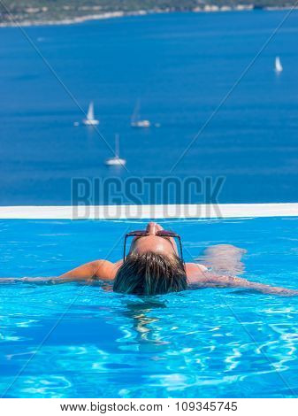 Woman in the infinity swimming pool in Greece