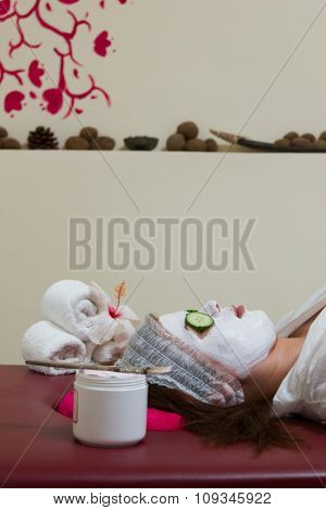 Woman with clay facial mask in beauty spa salon