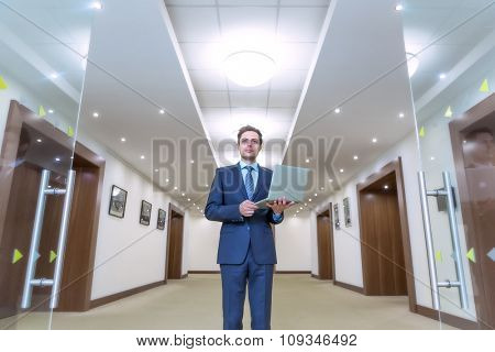 Young business man with laptop indoors