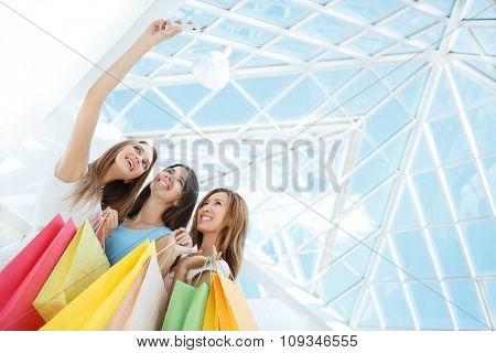 Young girls with shopping bags make self