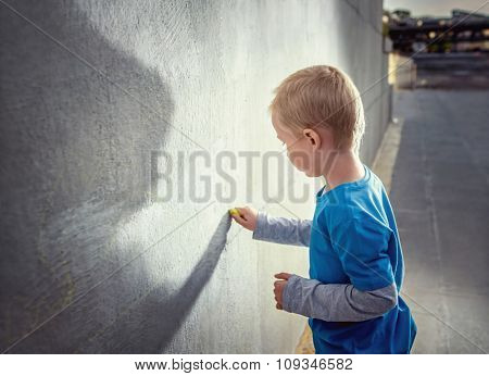 Painting little boy at the wall