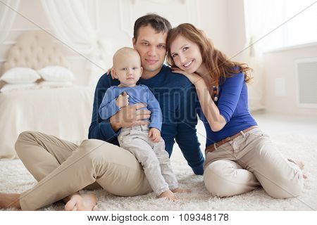 Home portrait of happy young family.