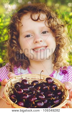 Beautiful Little Girl Holding A Basket Of Sweet Cherries.