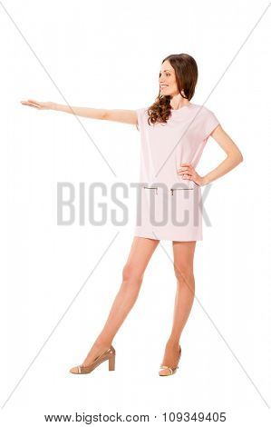 Young slim pretty woman in pink dress with outstretched hand isolated on white background