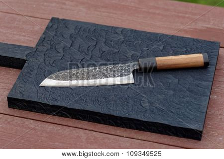 Knife on a black wooden cutting board