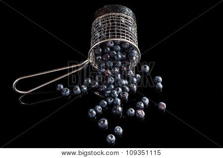 Blueberries spilled from cup strainer from side high angle