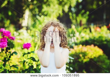 Little Girl Closed Face With Her Hands, Weeping, Or Playing Hide And Seek.