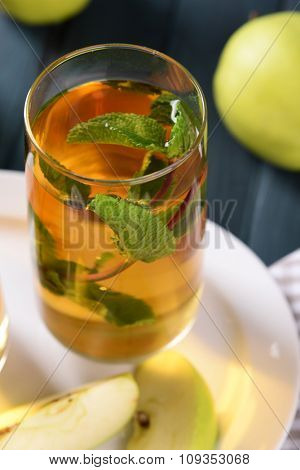 Glass of apple juice with fruits and fresh mint on table close up