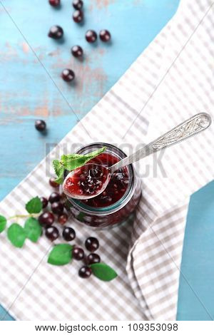 Jar of gooseberry jam on wooden table close-up