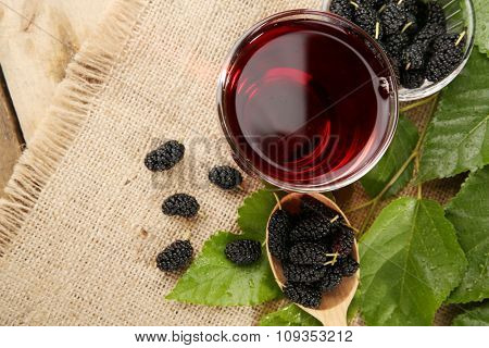 Glass of refreshing mulberry juice with berries on table close up
