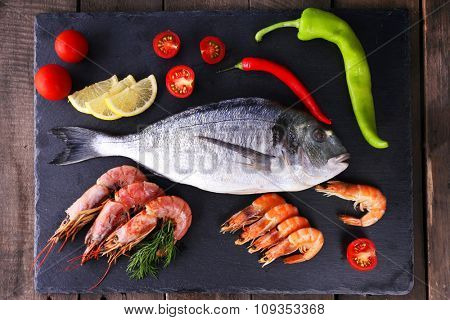 Dorado fish and other ingredients on parchment on wooden table, top view