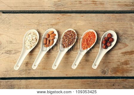 Different products in spoons on wooden table close up