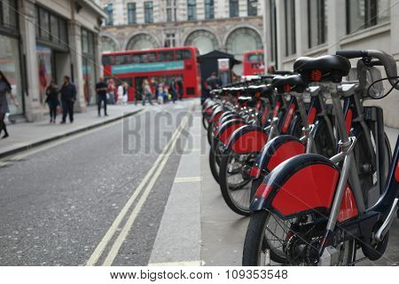 view of the bikes in the street of london ,with red bus in the background
