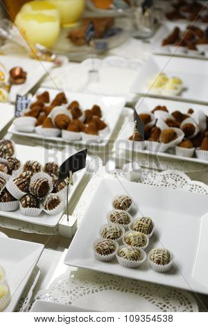 Delicious chocolate candies on plates on table close up