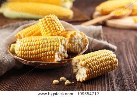 Ripe corn in wicker bowl on wooden background