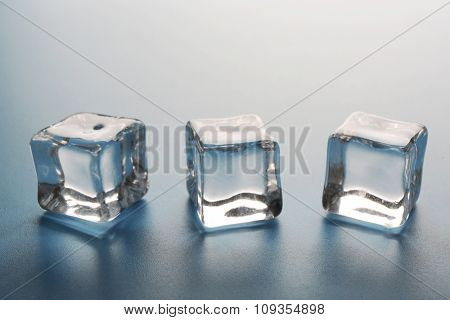Perfect ice cubes in a row on grey background, close up