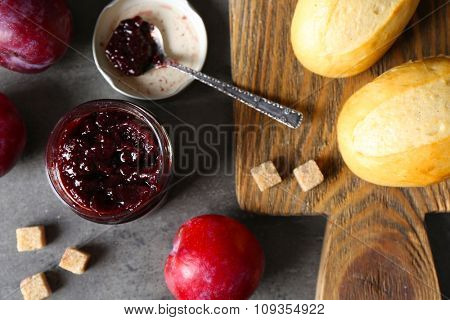 A jar of tasty jam, a spoon, plums, crackers on grey background and fresh buns on wooden tablet