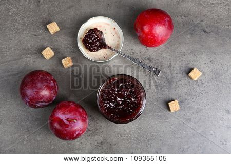 A jar of tasty jam, a spoon, plums and crackers on grey background