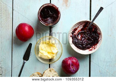 Tasty jam in the jar and bowl, butter, fresh bread, plums and tablet on blue wooden background