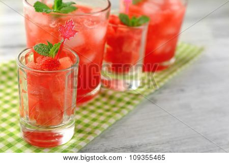 Cold watermelon desserts and drinks in glasses, on wooden table background
