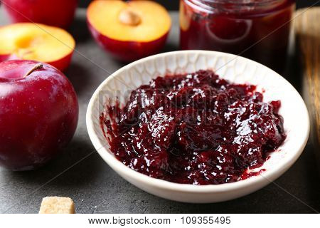 Tasty jam in the jar and on the plate, plums and crackers close-up