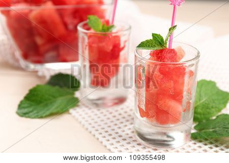 Cold watermelon pieces in glasses, on wooden table background