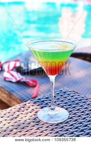 Cocktail on swimming pool background