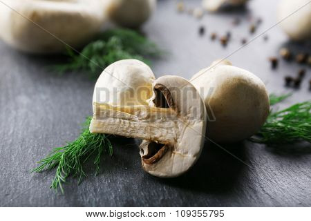 Champignon mushrooms, spices and dill on grey wooden background