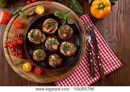 A frying pan with stuffed mushrooms and vegetables on the table, top view