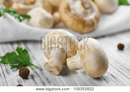 Champignon mushrooms and spices on white wooden background