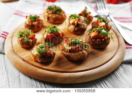 A wooden tablet with stuffed mushrooms on the table