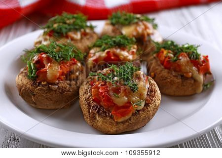 A plate with stuffed mushrooms on wooden background