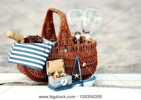 Picnic basket with bottle of wine on sand beach